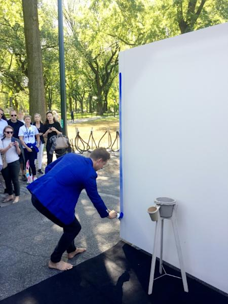 "Danish artist Jeppe Hein paints the first lines of his artwork ""Breathe with Me,"" whose installation is timed with the UN Climate Summit"