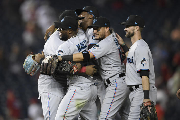 Miami Marlins' Starling Marte, second from left, Miguel Rojas, second from right, and others celebrate after the team's 3-1 win over the Washington Nationals in a baseball game Wednesday, July 21, 2021, in Washington. (AP Photo/Nick Wass)