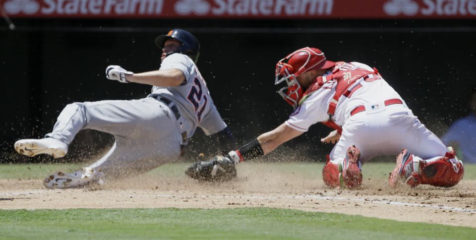 Detroit Tigers' JaCoby Jones, left, slides into home to avoid a tag by Los Angeles Angels catcher Jonathan Lucroy on a single by Niko Goodrum during the third inning of a baseball game in Anaheim, Calif., Wednesday, July 31, 2019. (AP Photo/Alex Gallardo)