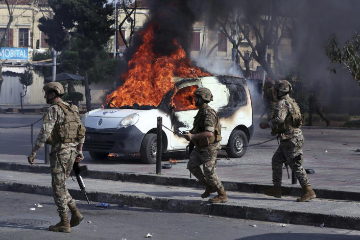 Lebanese army soldiers gather near a Lebanese internal security forces vehicle that was set on fire by anti-government protesters, in the northern city of Tripoli, Lebanon, Tuesday, April 28, 2020. Hundreds took part in the funeral of a young man killed in riots overnight in Tripoli that were triggered by the crash of Lebanon's national currency that sent food prices soaring. (AP Photo/Bilal Hussein)
