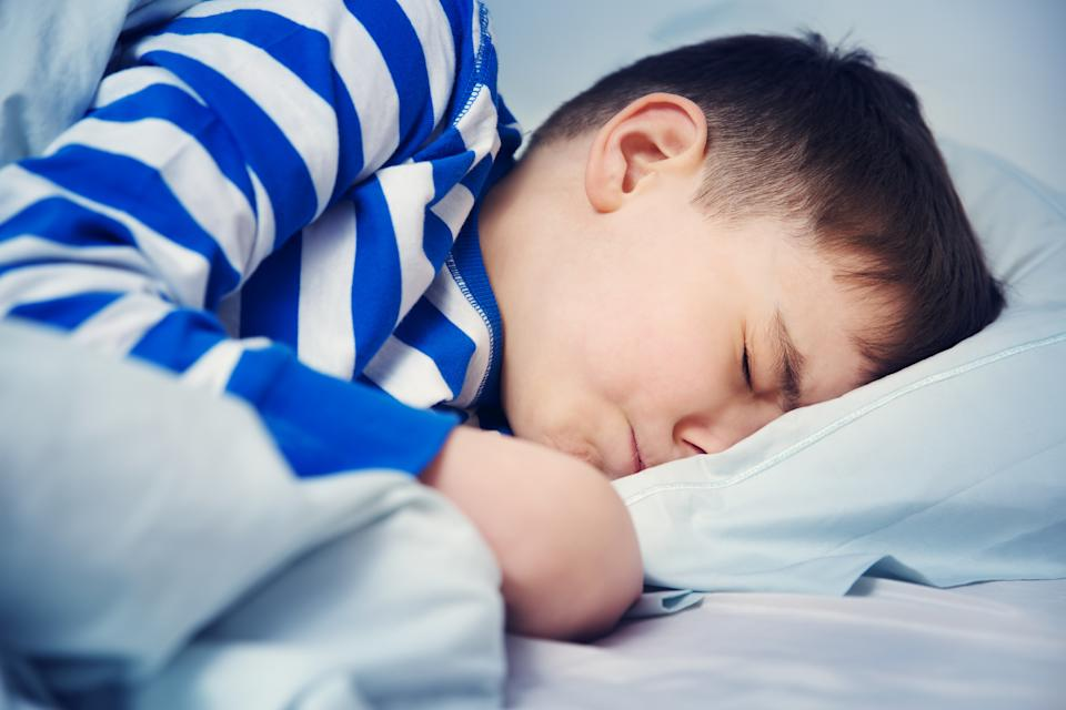 Boy sleeping in bed in pajamas. Child lying in bed on pillow at night.
