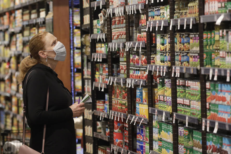Erin Call wears a mask as she shops for groceries at Harmons grocery store on April 3, 2020, in Salt Lake City. (AP Photo/Rick Bowmer)