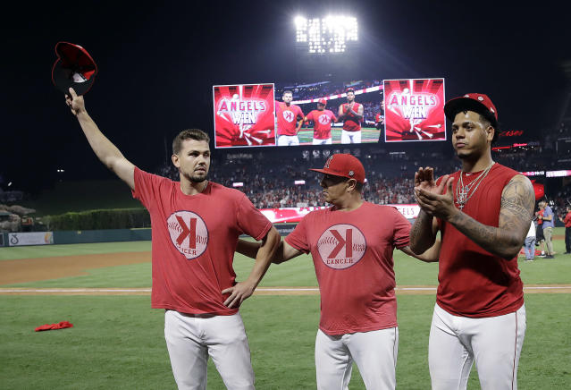 Los Angeles Angels starting pitcher Taylor Cole, left, and relief pitcher Felix Pena, right, alongside Pena's interpreter, middle, acknowledge the crowd's applause after a combined no-hitter against the Seattle Mariners during a baseball game Friday, July 12, 2019, in Anaheim, Calif. The Angels won 13-0. (AP Photo/Marcio Jose Sanchez)