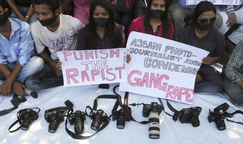 FILE - In this Saturday, Aug. 24, 2013 file photo, photojournalists sit with placards during a protest against the gang rape of a photojournalist in Mumbai, in Gauhati, India. A series of recent high-profile gang rape cases in India has ignited a debate: Are such crimes on the rise, or is it simply that more attention is being paid to a problem long hidden within families and villages? The answer, experts say, is both. Modernization is fueling a crisis of sexual assault in India, with increasingly independent women now working in factories and offices and stepping beyond the subservient roles to which they had traditionally been relegated. (AP Photo/Anupam Nath, File)