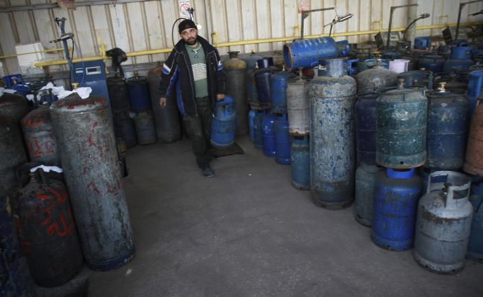 A Palestinian arranges empty cooking gas canisters in Gaza City, Wednesday, March 21, 2012. A test of wills between Egypt and Gaza's Hamas government has produced the worst energy crisis here in years: Gazans are enduring 18-hour-a-day blackouts and the fuel supply is running low. (AP Photo/Adel Hana)