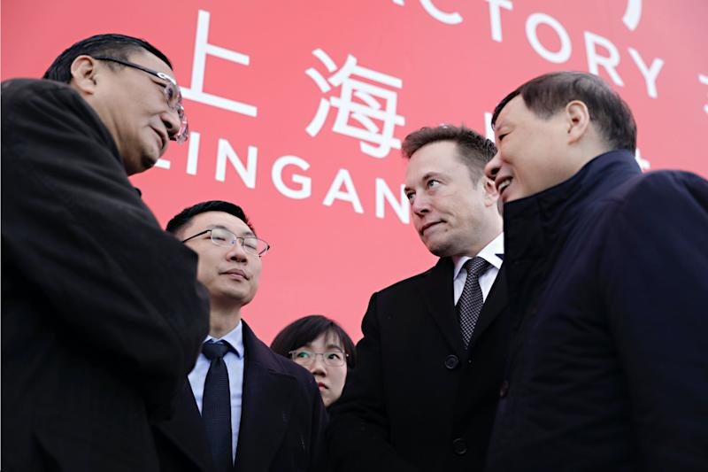 Robin Ren, vice president of sales at Tesla Inc., left, speaks with Elon Musk, chief executive officer, second right, and Ying Yong, mayor of Shanghai, right, following an event at the site of the company's manufacturing facility in Shanghai, China, on Monday, Jan. 7, 2019. (Photo: Qilai Shen/Bloomberg via Getty Images)