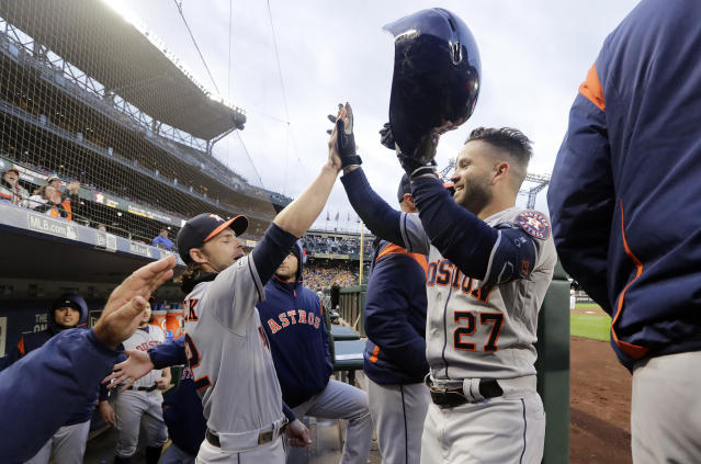 Houston Astros' Jose Altuve (27) is congratulated by Josh Reddick as he enters the dugout after hitting a solo home run against the Seattle Mariners in then fifth inning of a baseball game Saturday, April 13, 2019, in Seattle. (AP Photo/Elaine Thompson)