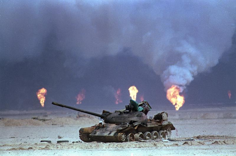 Image: A destroyed Iraqi tank rests near a series of oil well fires (David Longstreath / AP file)