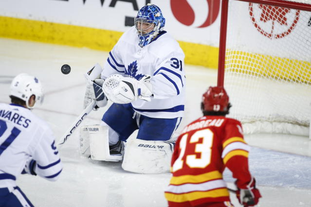 Toronto Maple Leafs goalie Frederik Andersen, left, deflects a shot from Calgary Flames' Johnny Gaudreau during the second period of an NHL hockey game, Thursday, Dec. 12, 2019 in Calgary, Alberta. (Jeff McIntosh/The Canadian Press via AP)