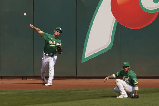 Oakland Athletics left fielder Mark Canha, left, throws the ball to the infield after making a catch at the wall hit by Chicago White Sox's Yoan Moncada during the third inning of Game 2 of an American League wild-card baseball series Wednesday, Sept. 30, 2020, in Oakland, Calif. Center fielder Ramon Laureano, right, backs up the play. (AP Photo/Eric Risberg)