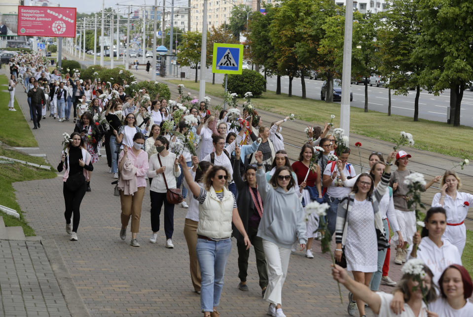 "Belarusian women rally in solidarity with protesters injured in the latest rallies against the results of the country's presidential election in Minsk, Belarus, Thursday, Aug. 13, 2020. Hundreds of people were back on the streets of Belarus' capital on Thursday morning, forming long ""lines of solidarity"" in protest against an election they say was rigged to extend the rule of the country's authoritarian leader and against a crackdown on rallies that followed the vote. (AP Photo/Sergei Grits)"