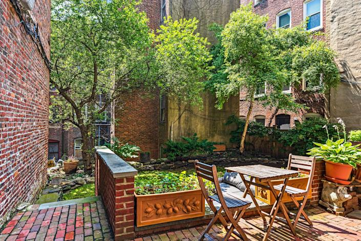 A courtyard outside of the home with trees and seating areas