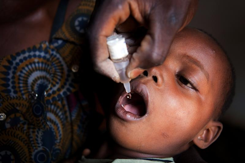A Democratic Republic of Congo Ministry of Health employee administers a polio vaccination to a child in the southern city of Lubumbashi, on October 28, 2010