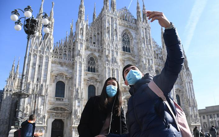 Tourists wearing protective face mask pose for a selfie in front of the Milan Cathedral, in Milan, northern Italy in February - DANIEL DAL ZENNARO/EPA-EFE/REX