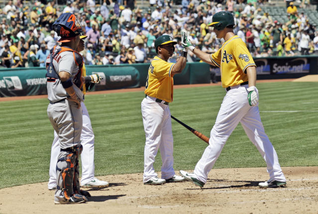 Oakland Athletics' Nate Freiman, right, celebrates his two-run home run with Alberto Callaspo, center, during the third inning of a baseball game against the Houston Astros on Thursday, Aug. 15, 2013, in Oakland, Calif. (AP Photo/Marcio Jose Sanchez)