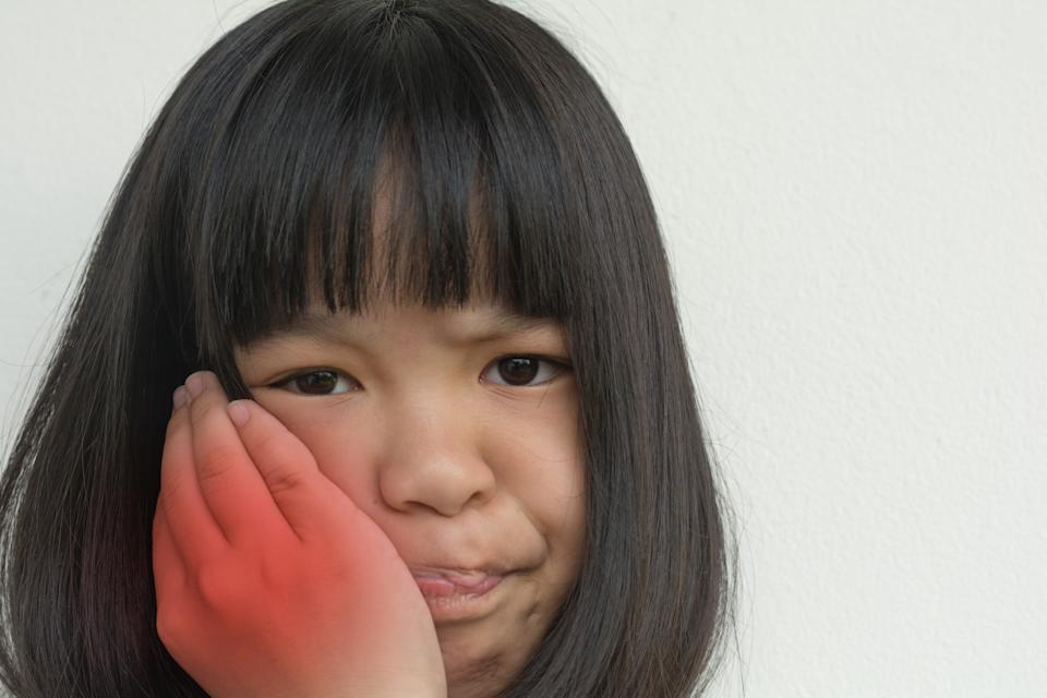 TMD and TMJ healthcare concept: Temporomandibular Joint and Muscle Disorder. Asia child kid girl hand on cheek face as suffering from facial pain, mumps or toothache