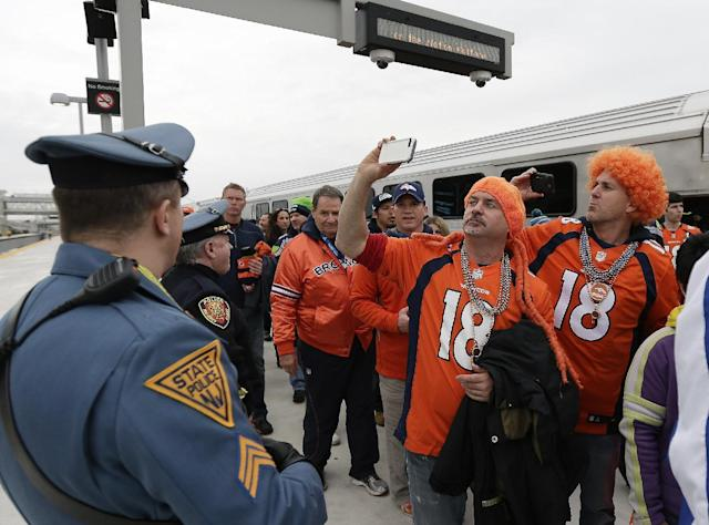 Denver Broncos fans take pictures of the stadium as they arrive at the Meadowlands Rail Station before the NFL Super Bowl XLVIII football game Sunday, Feb. 2, 2014, in East Rutherford, N.J. (AP Photo/Gregory Bull)