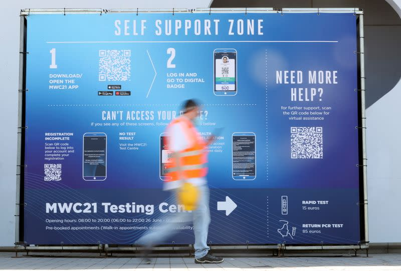 Worker walks past a sign ahead of the Mobile World Congress (MWC) at Fira de Barcelona