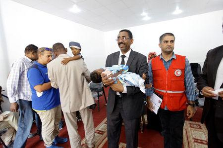 Members of Libyan Red Crescent hand over the children of Sudanese Islamic State members who operated in Libya, to a Sudanese official, in Misrata, Libya August 20, 2017. REUTERS/Ismail Zitouny
