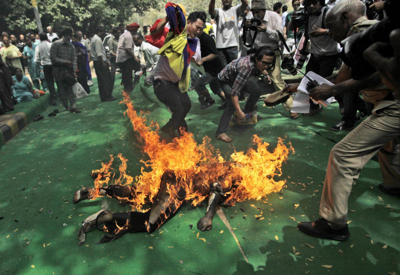 Fellow protesters try to extinguish the fire as a Tibetan man, identified as Jampa Yeshi, is engulfed in flames after self-immolating at a protest in New Delhi, India, ahead of Chinese President Hu Jintao's visit to the country Monday, March 26, 2012. The Tibetan activist lit himself on fire at the gathering and was rushed to hospital with unknown injuries, reports said. (AP Photo/Manish Swarup)