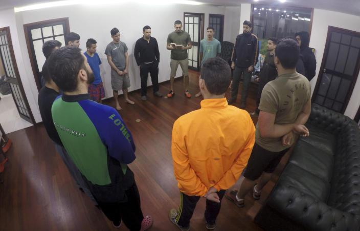 In this Nov. 8, 2019 photo, Venezuelan soldiers, who took part in a failed April rebellion against Nicolas Maduro, stand in a prayer circle inside Panama's Embassy in Caracas, Venezuela. The group of 16 Venezuelan guardsmen who were holed up for seven months in the foreign embassy after revolting against Maduro said they have managed to flee the country. (AP Photo)