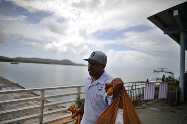 <p>Luis Menendez, a mail man for the U.S. Postal Service, receives mail by boat at a narea affected by Hurricane Maria in the island of Vieques, Puerto Rico, Oct. 7, 2017. (Photo: Carlos Barria/Reuters) </p>