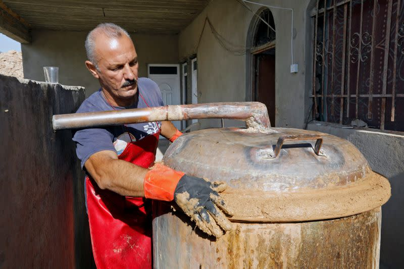 Saad Hussein, an Iraqi Yazidi, puts the clay in the process of producing Arak liquor out of dates, on the outskirts of Mosul