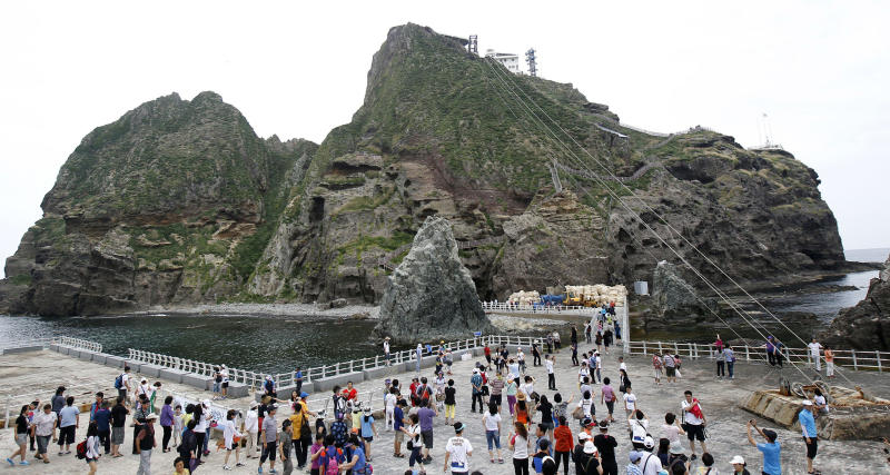 South Korean tourists are on a tour of Seodo, part of the disputed Dokdo islets, in the East Sea, South Korea, Monday, Aug. 1, 2011. South Korea has banned three Japanese lawmakers from entering the country after they arrived at a Seoul airport in an attempt to travel near the islands whose possession is in dispute between the neighbors. Seen in rear is Dongdo, also part of the disputed islands. (AP Photo/Yonhap, Lee Sang-hack)   KOREA OUT