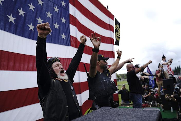 """FILE - In this Sept. 26, 2020 file photo, members of the Proud Boys, including leader Enrique Tarrio, second from left, gesture and cheer on stage as they and other right-wing demonstrators rally in Portland, Ore. President Donald Trump didn't condemn white supremacist groups and their role in violence in some American cities this summer. Instead, he said the violence is a """"left-wing"""" problem and he told one far-right extremist group to """"stand back and stand by."""" His comments Tuesday night were in response to debate moderator Chris Wallace asking if he would condemn white supremacists and militia groups. Trump's exchange with Democrat Joe Biden left the extremist group Proud Boys celebrating what some of its members saw as tacit approval."""