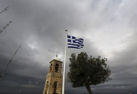 Greek flag flutters between Saint George's bell tower and an olive tree atop the Lycabettus hill