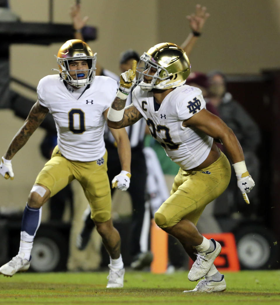 Notre Dame running back Kyren Williams (23) and wide receiver Braden Lenzy (0) celebrate a touchdown during the second half of an NCAA college football game against Virginia Tech in Blacksburg, Va., Saturday, Oct. 9, 2021. (AP Photo/Matt Gentry)