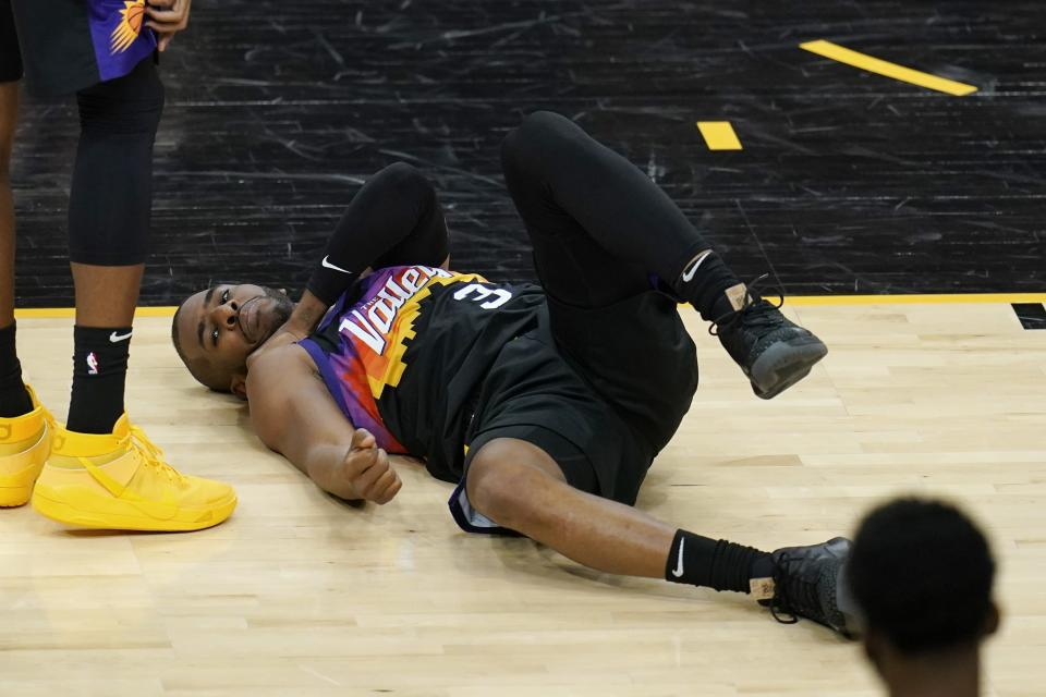An injured Phoenix Suns guard Chris Paul grabs his shoulder during the first half of Game 1 of their NBA basketball first-round playoff series against the Los Angeles Lakers Sunday, May 23, 2021, in Phoenix. (AP Photo/Ross D. Franklin)