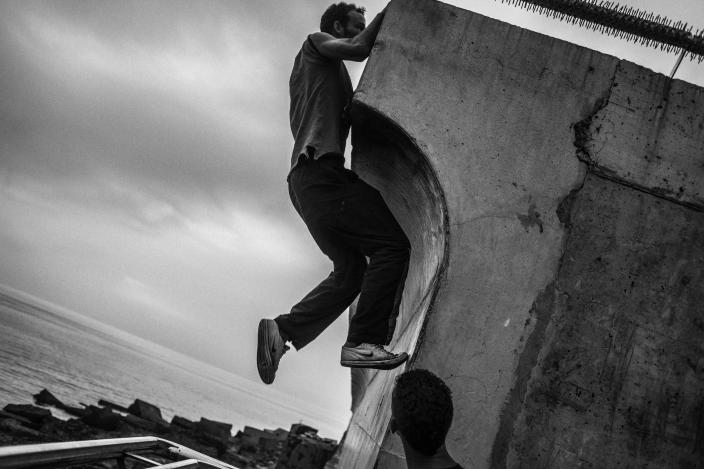 A young migrant tries to jump the wall of the port of Melilla in 2014. (Photo: José Colón/MeMo for Yahoo News)