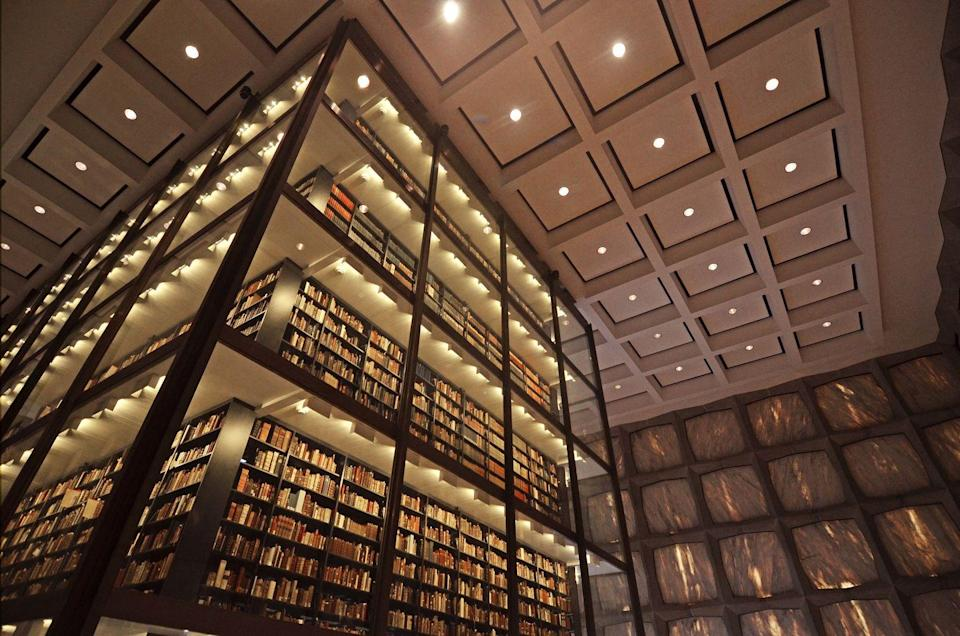 """<p>What's as awe-inducing as the number of rare books <a href=""""http://beinecke.library.yale.edu"""" rel=""""nofollow noopener"""" target=""""_blank"""" data-ylk=""""slk:Yale University's Beinecke Library"""" class=""""link rapid-noclick-resp"""">Yale University's Beinecke Library</a> holds (about 1 million, for the record)? To be frank, what holds them: A large glass tower that stands tall at the center of this marble, granite and bronze structure. </p>"""