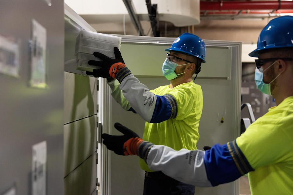 Workers remove COVID-19 vaccine kept in ultracold refrigerators at Pfizer's manufacturing site in Kalamazoo.