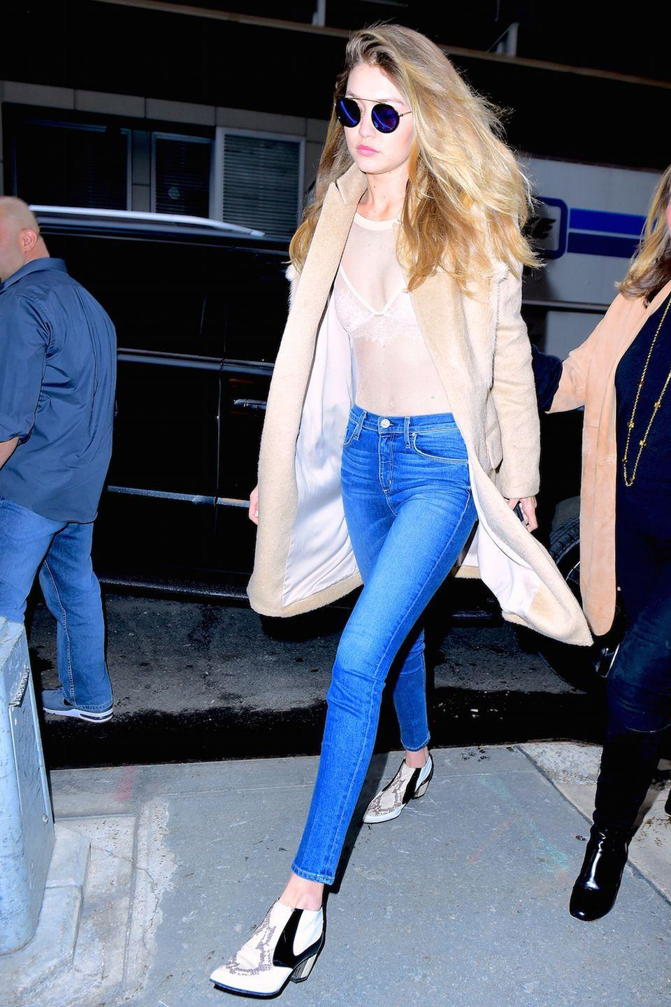 <p>The model maneuvered a crowd of screaming fans as she left her NYC hotel with boyfriend Zayn Malik, wearing a sheer nude bodysuit over a lacy bra with skinny denim, a camel coat and Rodarte ankle boots. </p>