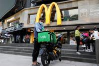 FILE PHOTO: A GrabFood rider gets ready for a delivery outside a McDonald?s restaurant, amid the coronavirus disease (COVID-19) outbreak in Kuala Lumpur
