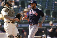 Cleveland Indians' Eddie Rosario, right, scores as Seattle Mariners catcher Luis Torrens looks on in the sixth inning of a baseball game Sunday, May 16, 2021, in Seattle. (AP Photo/Elaine Thompson)