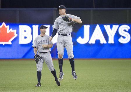 Mar 29, 2018; Toronto, Ontario, CAN; New York Yankees right fielder Aaron Judge (99) celebrates the win with New York Yankees left fielder Brett Gardner (11) at the end of the Toronto Blue Jays home opener at Rogers Centre. The New York Yankees won 6-1. Mandatory Credit: Nick Turchiaro-USA TODAY Sports