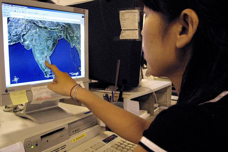 An office worker checks out a map on Google's satellite image service, in Hong Kong, on October 18, 2005 (AFP Photo/Laurent Fievet)