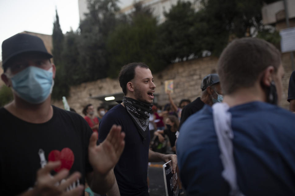 Shachar Oren, 25, chants slogans during a protest against Israel's Prime Minister Benjamin Netanyahu outside his residence in Jerusalem, Tuesday, Aug. 4, 2020. The boisterous rallies against Netanyahu have brought out a new breed of first-time protesters -- young, middle-class Israelis who have little history of political activity but feel that Netanyahu's scandal-plagued rule and his handling of the coronavirus crisis have robbed them of their futures. (AP Photo/Maya Alleruzzo)