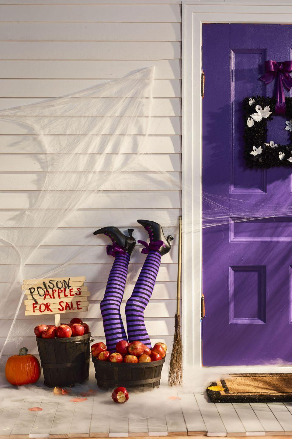"""<p>Flank your front door with apple barrels, then push in pool noodles that are outfitted in striped stockings and pointy heels for a bewitching outdoor decoration.</p><p>1. Cut two pool noodles to leg size (about <span>30</span>"""" tall).</p><p>2. To make knees, draw a <span>3</span>"""" half-circle in middle of each leg and cut the shape out. Pull edges together and secure with duct tape.</p><p>3. Tape quilt batting around pool noodles, adding extra layers to hip and thigh areas and an almond shape where it bends to complete knee. Use more tape to smooth out form.</p><p>4. Pull tights over legs. Stuff witch boots with batting and secure to legs by tying laces tightly.</p><p>5. To make sign, hot-glue six paint stirrers together to form a jagged rectangle, then hot-glue another stirrer to the back as a signpost. Paint on a phrase like """"Poison Apples for Sale.""""</p>"""