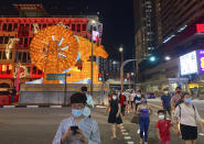 Pedestrians cross a street with a lit giant ox display to welcome the Lunar New Year at Chinatown in Singapore in Singapore Friday, Feb. 12, 2021. With Malaysian workers and students stranded in the city state over the Lunar New Year due to coronavirus travel restrictions, the Malaysian Association in Singapore has called on Malaysians to treat students to a meal. (AP Photo/Annabelle Liang)