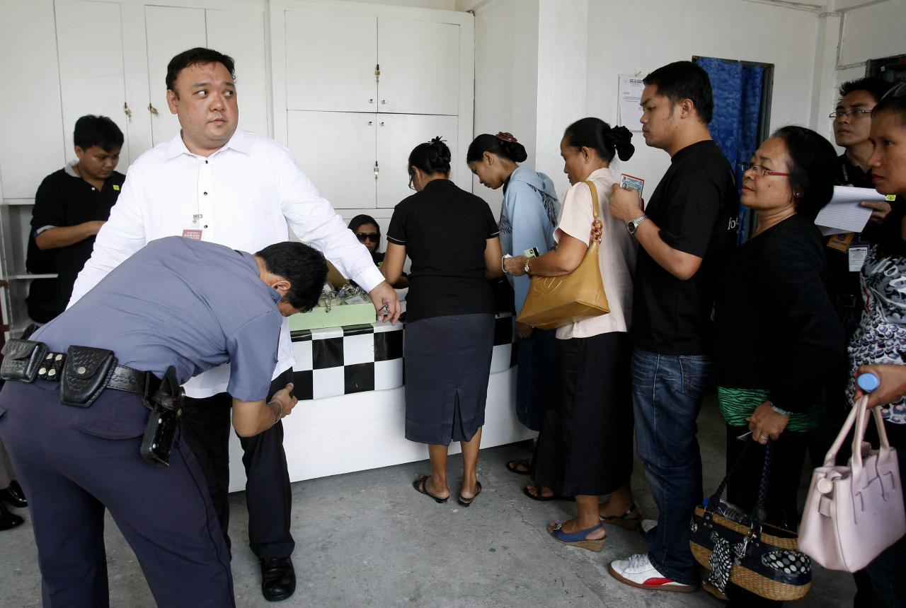 Harry Roque, left, the legal counsel for the massacre of 57 people, including 32 journalists and staff, in Maguindanao province in southern Philippines, is frisked by a jail guard as relatives of the victims queue up to enter the court for the resumption of the trial at Camp Bagong Diwa in Taguig city, east of Manila, Philippines on the 2nd anniversary of the massacre Wednesday Nov. 23, 2011. Andal Ampatuan Sr., patriarch of a powerful Maguindanao clan and former governor of an autonomous Muslim region, is among nearly 100 suspects being tried on murder charges in the massacre, together with his sons and relatives. (AP Photo/Bullit Marquez)