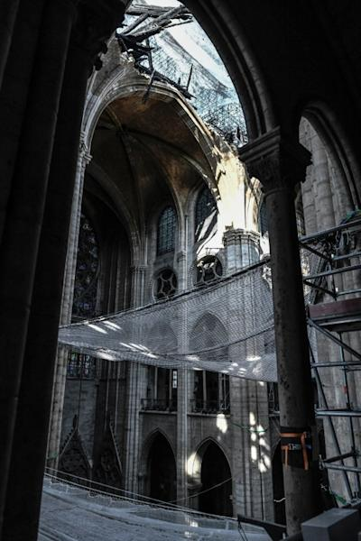 Great protective nets have been hung to prevent objects falling from the roof and causing damage, and staff must guard against lead poisoning because of the contamination caused by the old melted roof (AFP Photo/STEPHANE DE SAKUTIN)