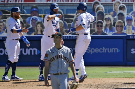 Los Angeles Dodgers' A.J. Pollock, right, is congratulated by Justin Turner, left, and Cody Bellinger after hitting a three-run home run as San Francisco Giants relief pitcher Tyler Rogers walks off the mound during the seventh inning of a baseball game Sunday, Aug. 9, 2020, in Los Angeles. (AP Photo/Mark J. Terrill)