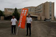 Daisuke Anbo (R) and Ryuji Maeta, members of a group aiming to maintain the delivery service in the city, holding a banner pose for a photograph in front of a general hospital in Kazuno, Akita prefecture, northern Japan June 20, 2018. Picture taken June 20, 2018. REUTERS/Kiyoshi Takenaka