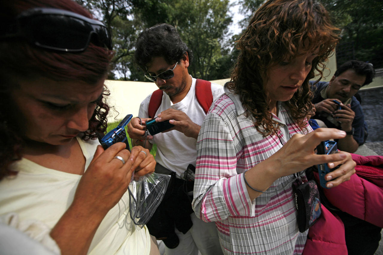 In this photo taken Sept. 7, 2011, blind people feel their cameras during a photography workshop at a park in Mexico City. They form part of a group of 30 visually impaired or blind people learning photography with the help of the Mexico City foundation Ojos Que Sienten, or Eyes That Feel. (AP Photo/Marco Ugarte)