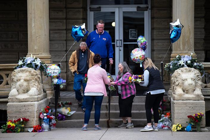 Community members place flowers and balloons outside of the main entrance to the Anamosa State Prison, on Wednesday, March 24, 2021, a day after a nurse and correctional officer were killed while on duty, in Anamosa, Iowa.