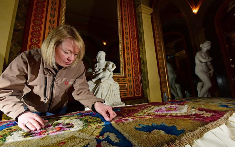English Heritage's head conservator Caroline Rawson examining moth damage to a carpet at Brodsworth Hall in Yorkshire - PA